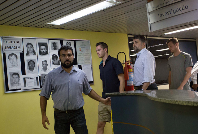 Accompanied by Brazilian lawyer Sergio Viegas, second from right, American Olympic swimmers Gunnar Bentz, center, and Jack Conger, right, leave the police station at Rio International airport earl ...