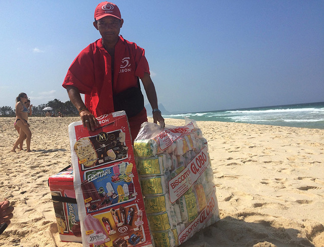 A vendor sells Biscoito Globo and other items on a beach during the 2016 Summer Olympics in Rio de Janeiro, Brazil, Friday, Aug. 19, 2016. The starchy, puffy treats made with coconut oil, milk, wa ...
