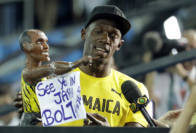 Jamaica's Usain Bolt holds a model of himself as he celebrates winning the gold medal in the men's 4x100-meter relay final during the athletics competitions of the 2016 Summer Olympics at the Olym ...