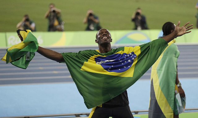 Jamaica's Usain Bolt holds the flag of Brazil after winning the gold medal in the men's 4x100-meter relay final during the athletics competitions of the 2016 Summer Olympics at the Olympic stadium ...