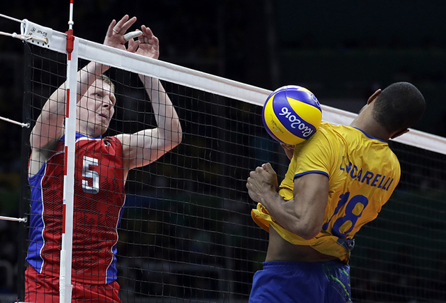 Russia's Sergey Grankin, left, scores past Brazil's Ricardo Lucarelli during a men's semifinal volleyball match at the 2016 Summer Olympics in Rio de Janeiro, Brazil, Friday, Aug. 19, 2016. (AP Ph ...