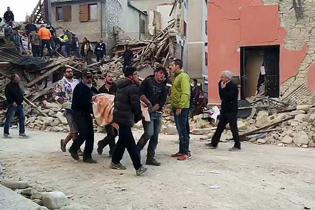 This still image taken from video shows rescuers recover a victim from a crumbled building in Amatrice, central Italy, where a 6.1 earthquake struck just after 3:30 a.m., Wednesday, Aug. 24, 2016. ...