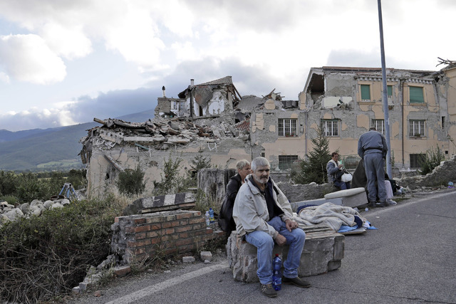 People sit on the side of a road as collapsed buildings are seen in the background following an earthquake, in Amatrice, Italy, Wednesday, Aug. 24, 2016. (Alessandra Tarantino/AP)