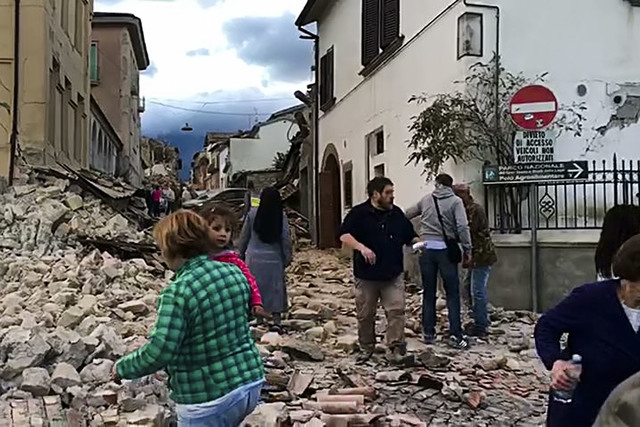 This still image taken from video shows survivors and rescuers wandering in the center of Amatrice, central Italy, where a 6.1 earthquake struck just after 3:30 a.m., Wednesday, Aug. 24, 2016. The ...