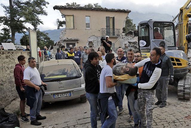 A man is carried out on a stretcher as a collapsed building is seen in the background following an earthquake in Amatrice, Italy, Wednesday, Aug. 24, 2016. (Alessandra Tarantino/AP)