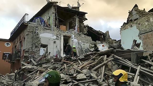 This still image taken from video shows rescuers searching a collapsed building in Amatrice, central Italy, where a 6.1 earthquake struck just after 3:30 a.m., Wednesday, Aug. 24, 2016. (AP Photo)