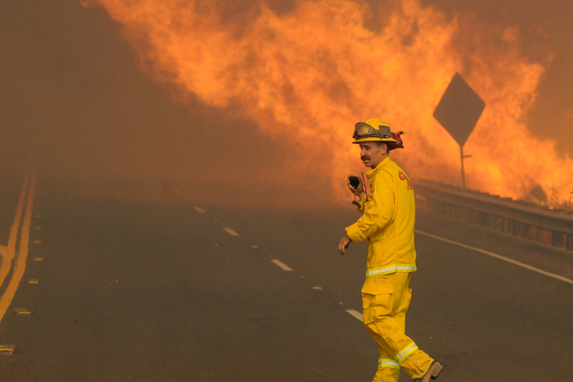 A CalFire firefighter begins clearing Highway 138 east of the Interstate 15 as a wildfire burns in California, Tuesday, Aug. 16, 2016. The fire forced the shutdown of a section of Interstate 15, t ...
