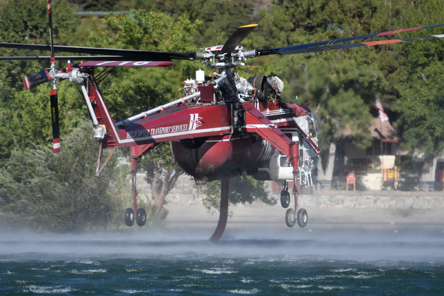 A Helicopter Transport Services aircraft gathers water at the Mountain Lakes RV Camping Club in Lytle Creek, Creek, Calif., Tuesday, Aug. 16, 2016, to fight a wildfire. (David Pardo/The Daily Pres ...