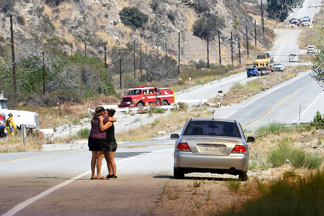 Two women hug along Cajon Boulevard as a wildfire burns nearby in Devore, Calif., on Wednesday, Aug. 17, 2016. A wildfire with a ferocity never seen before by veteran California firefighters raced ...