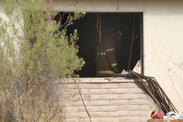 A Clark County firefighter surveys the damage of a house fire at 901 Apache Lane on Monday, Aug. 1, 2016. (Bizuayehu Tesfaye/Las Vegas Review-Journal Follow @bizutesfaye)