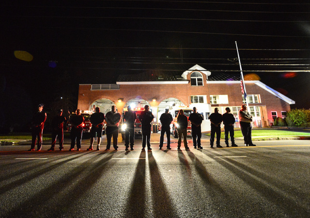 Members of the Bellows Falls Fire Department stand in front of their station as they pay respect to Justin Beebe early Wednesday in Vermont. (Kristopher Radder/Brattleboro Reformer via AP)