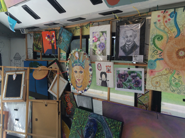 Artwork hangs along the walls of the Artz-to-Go bus, which takes mobile art classes to schools, local events and parks, and also  serves as a traveling gallery.  (Joan Patterson/Special to the Las ...