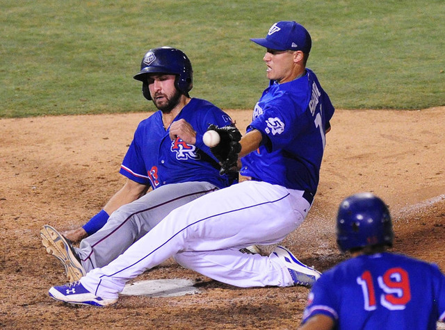 Round Rock base runner Joey Gallo scores the game's tying run on a wild pitch while Las Vegas pitcher Paul Sewald fields the throw in the ninth inning of their Triple-A minor league baseball game  ...