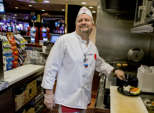 Mel Jones, who has worked for 35 years at Binion's Gambling Hall & Hotel, 128 Fremont St., prepares a hamburger at  the deli on Friday, Aug. 12, 2016. The downtown casino is celebrating its 65 ...