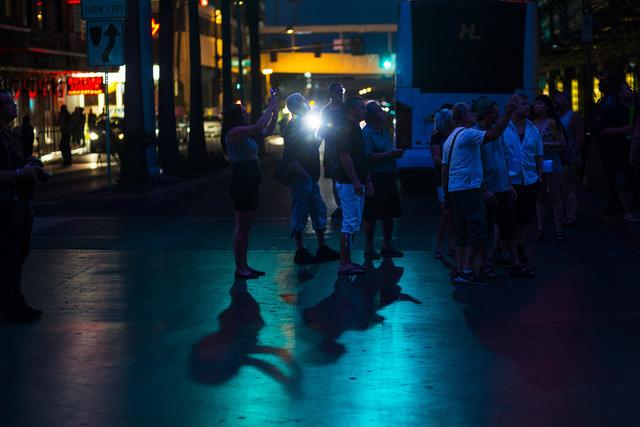 People take photos along Casino Center Avenue outside of Binion's hotel-casino, left, in downtown Las Vegas on Wednesday, Aug. 10, 2016. Chase Stevens/Las Vegas Review-Journal Follow @csstevensphoto