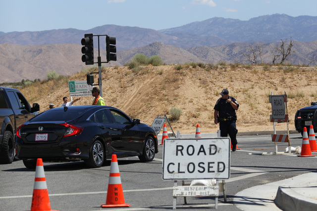 A California Highway Patrol officer directs traffic away from Summit Valley Road, which is closed due to the Blue Cut Fire in Hesperia, Calif., on Wednesday, Aug. 17, 2016. Brett Le Blanc/Las Vega ...