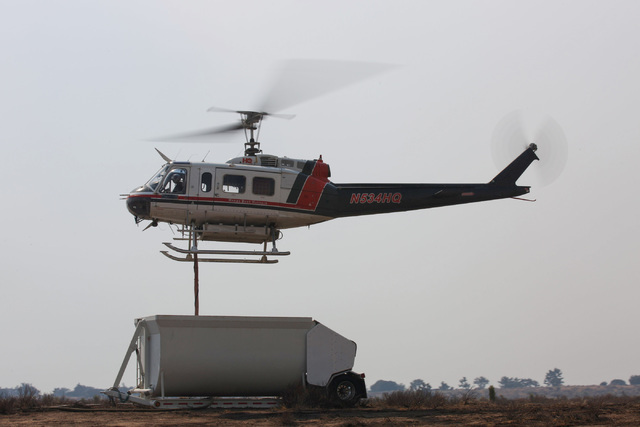 A Bell-205 from Heaps Peak Helitack refills its tank with water to drop on the Blue Cut Fire in Hesperia, Calif., on Wednesday, Aug. 17, 2016. Brett Le Blanc/Las Vegas Review-Journal Follow @blebl ...
