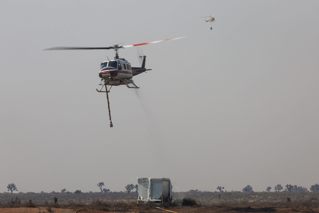 A Bell 205 helicopter pulls away from filling its tank as another helicopter approaches the refill station in Hesperia, Calif., on Wednesday, Aug. 17, 2016. Brett Le Blanc/Las Vegas Review-Journal ...