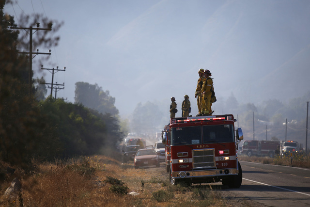 Firefighters watch for flareups from atop a fire engine at the Blue Cut Fire in Cajon Pass, Calif., on Thursday, Aug. 18, 2016. As of 6 p.m. Thursday, the fire is almost 36,000 acres and is 22 per ...