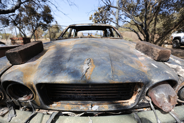 A melted jaguar emblem still adorns the hood of a car lost in the Blue Cut Fire on the property of the Chavez family in Oak Hills, Calif., on Saturday, Aug. 20, 2016. Firefighters were able to sav ...