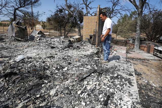 Jose Chavez, 46, stands in the rubble of his guest house that was brought down by the Blue Cut Fire in Oak Hills, Calif., on Saturday, Aug. 20, 2016. Firefighters were able to save Chavez family's ...