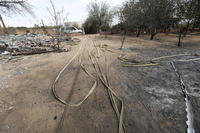 Fire hoses run through the property of the Chavez Family in Oak Hills, Calif., on Saturday, Aug. 20, 2016. Firefighters were able to save Chavez family's house (Brett Le Blanc/Las Vegas Review-Jou ...