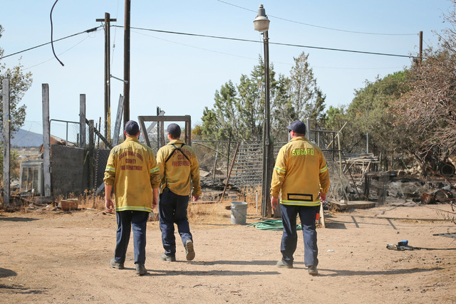 San Bernardino County firefighters look for hot spots on the Chavez family's property in Oak Hills, Calif., on Saturday, Aug. 20, 2016. Firefighters were able to save Chavez family's house, but th ...