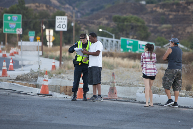 A safety officer helps bystanders navigate road closures near Interstate 15 on Wednesday, August 17, 2016, north of San Bernardino, Calif., due to wildfires near the freeway. Loren Townsley/Las Ve ...