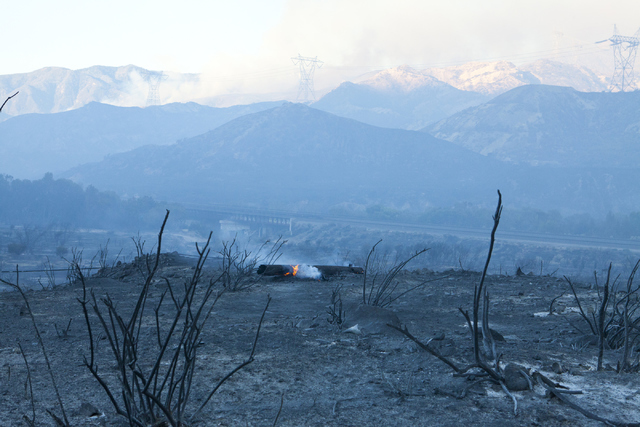 Power lines on Cajon Road continue to burn as Blue Cut Fire spreads west of Interstate 15 on Wednesday, August 17, 2016, north of San Bernardino, Calif. Northbound and southbound I-15 remains clos ...