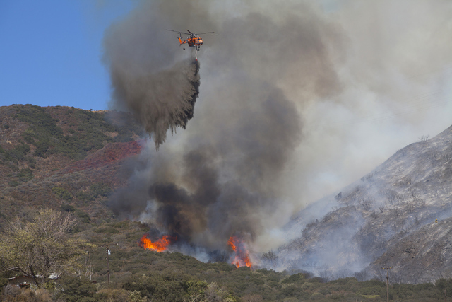 A helicopter drops water on the Blue Cut Fire in the Cajon Pass, north of San Bernardino, Calif., on Wednesday, August 17, 2016. Loren Townsley/Las Vegas Review-Journal Follow @lorentownsley