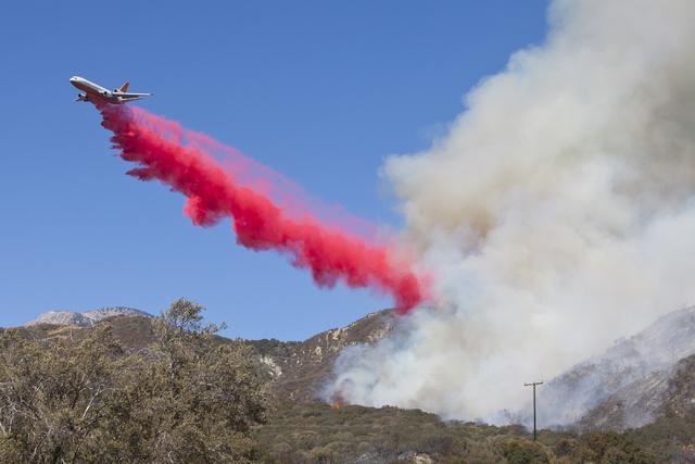 A bomber drops fire retardant on the Blue Cut Fire in the Cajon Pass, north of San Bernardino, Calif., on Wednesday, August 17, 2016. Loren Townsley/Las Vegas Review-Journal Follow @lorentownsley