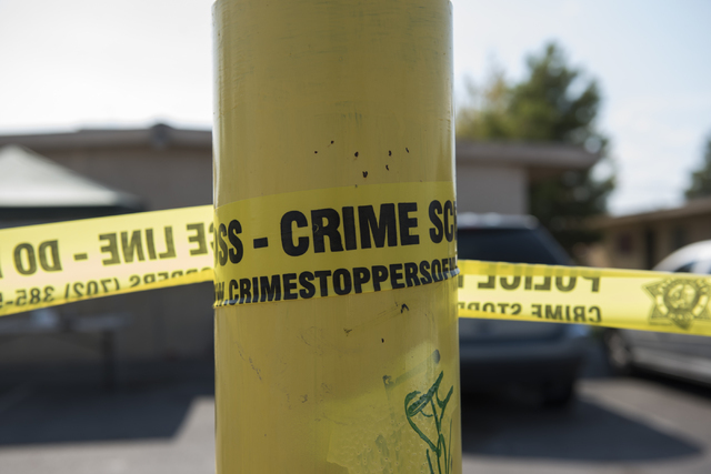 Caution tape is wrapped around a pole near the corner of Covey Lane and Irwin Avenue where a deceased body of a male in his 30s was found in North Las Vegas on Saturday, Aug. 20, 2016. The investi ...