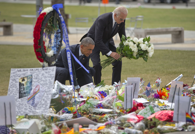 President Barack Obama and Vice President Joe Biden place flowers down during their visit to a memorial to the victims of the Pulse nightclub shooting, Thursday, June 16, 2016 in Orlando, Fla. Off ...