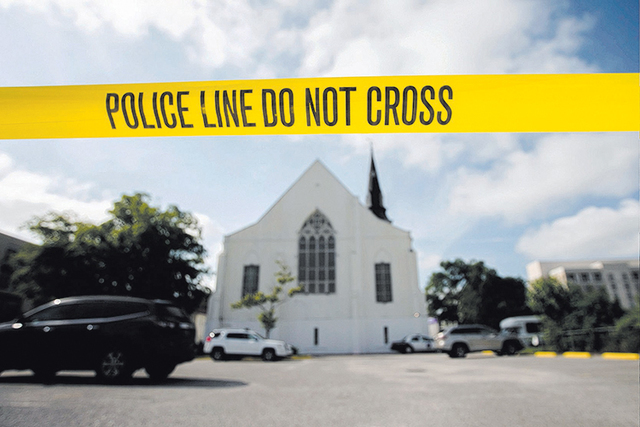 Police tape surrounds the parking lot behind the AME Emanuel Church, a predominantly black church, as FBI forensic experts work at the crime scene where nine people where shot by white suspect Dyl ...