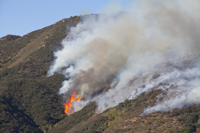 The Blue Cut Fire burns west of Interstate 15 at the Cajon Boulevard exit on Thursday, August 18, 2016, north of San Bernardino, Calif. Northbound I-15 is open, but southbound Interstate 15 remain ...