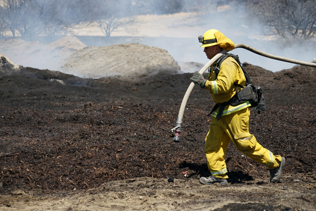 Firefighters water down scorched compost material at a property burned near Phelan, Calif., on Friday, Aug. 19, 2016. (Christine Armario/The Associated Press)