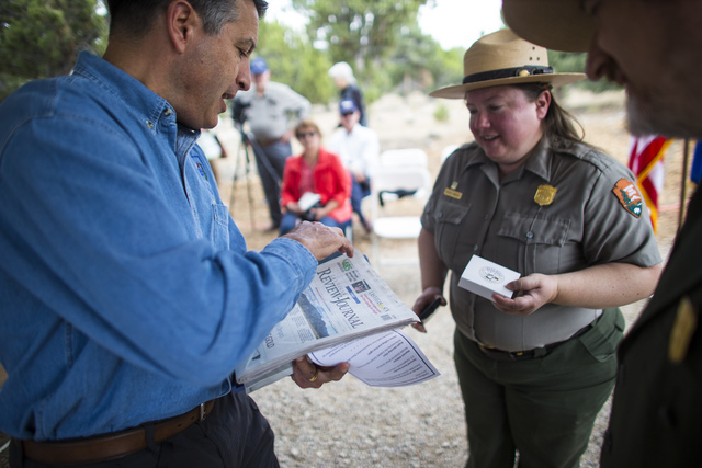 Gov. Brian Sandoval, left, holds a copy of the Review-Journal to be placed in a time capsule for the National Park Service centennial celebration as Great Basin National Park Chief of Interpretati ...