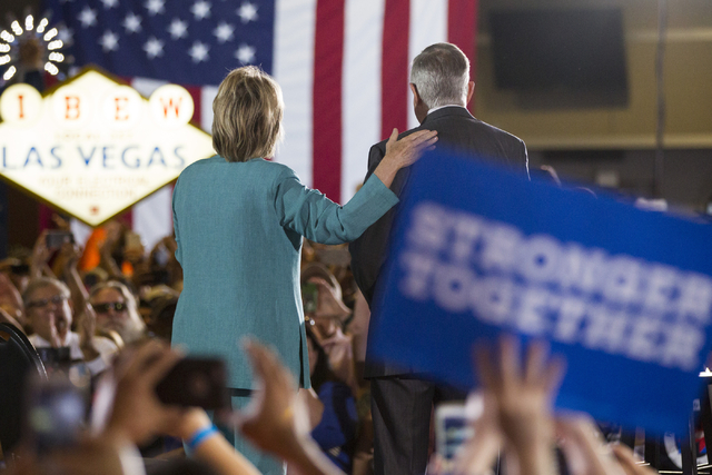 Democratic presidential nominee Hillary Clinton, left, and U.S. Sen. Harry Reid take the stage for a campaign rally at the International Brotherhood of Electrical Workers headquarters on Thursday, ...