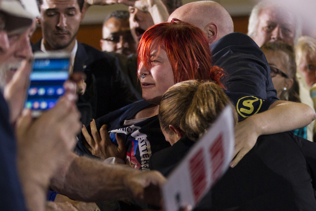 An animal activist who jumped over a barrier to get to Democratic presidential candidate Hillary Clinton is restraint by Secret Service agents during a campaign rally at the International Brotherh ...