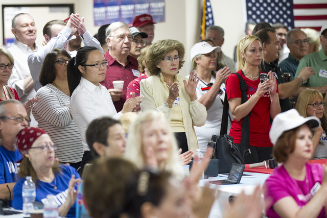 People listen to former Arizona Gov. Jan Brewer during the grand opening for the new campaign office for Republican presidential candidate Donald Trump in Las Vegas on Saturday, Aug. 27, 2016, in  ...