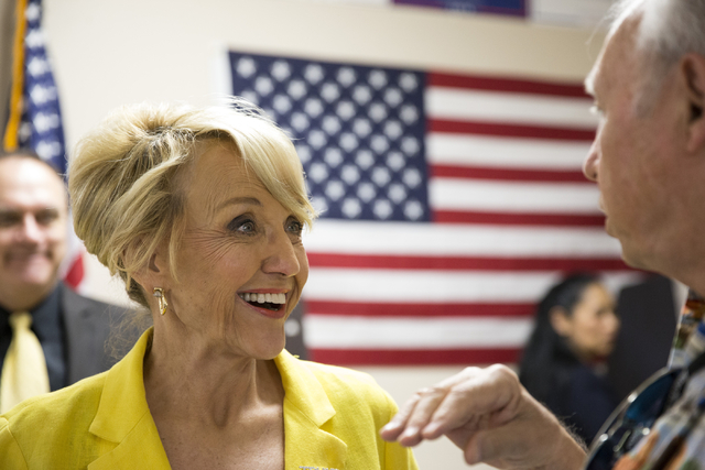 Former Arizona Gov. Jan Brewer speaks to a supporter during the grand opening for the new campaign office for Republican presidential candidate Donald Trump in Las Vegas on Saturday, Aug. 27, 2016 ...