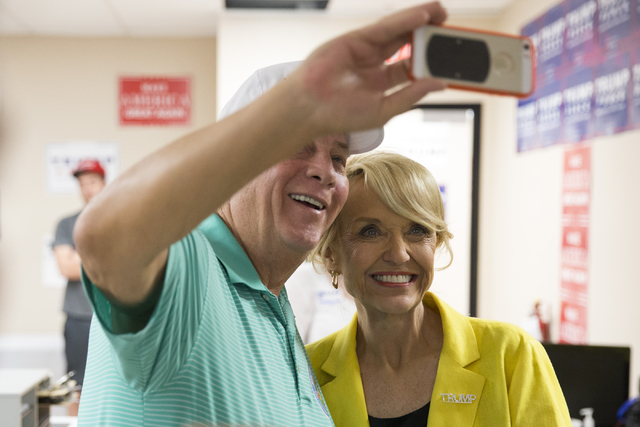 Former Arizona Gov. Jan Brewer, right, takes a photo with local businessman Dan Stansbury during the grand opening for the new campaign office for Republican presidential candidate Donald Trump in ...