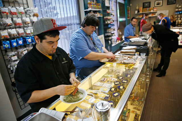 Employees roll joints behind the sales counter at Medicine Man marijuana dispensary in late December, just days before the business opened as a recreational outlet. Medicine Man was among the firs ...