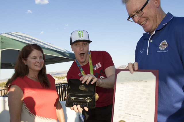 BMX Olympic gold medalist Connor Fields, center, shows off his key with Councilwoman Debra March, left, and Henderson Mayor Andy Haffen after a celebration at the Whitney Mesa BMX Track on Tuesday ...