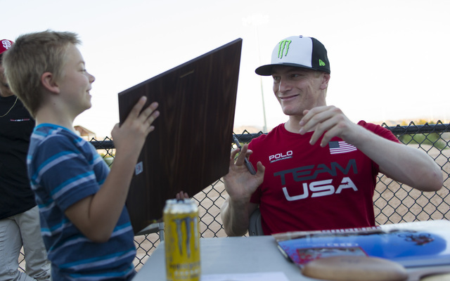 BMX Olympic gold medalist Connor Fields sign a poster for Las Vegas resident Chance Hester, 9, after a celebration at the Whitney Mesa BMX Track on Tuesday, Aug. 30, 2016, in Henderson. Connor rec ...