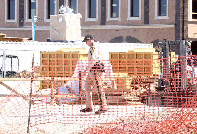 A Las Vegas police officer investigates after a construction worker died after scaffolding at Tivoli Village at 302 S. Rampart Blvd. collapsed on Monday, Aug. 22, 2016, causing the man to fall. Bi ...