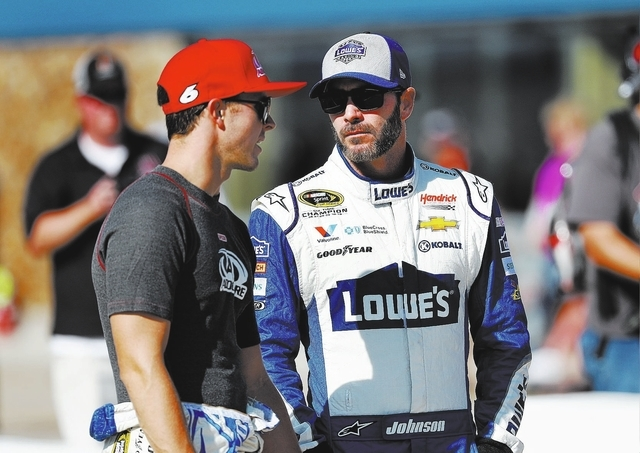 Trevor Bayne, left, talks with Jimmie Johnson before qualifications for the NASCAR Sprint Cup Series auto race at Michigan International Speedway, in Brooklyn, Mich., Friday, Aug. 26, 2016. (AP Ph ...