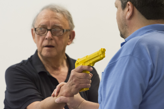 Instructor Roland Rogers, left, and volunteer Anthony Radel demonstrate self-defense moves against an attacker with a gun during a class for senior citizens at Metropolitan Police Department headq ...