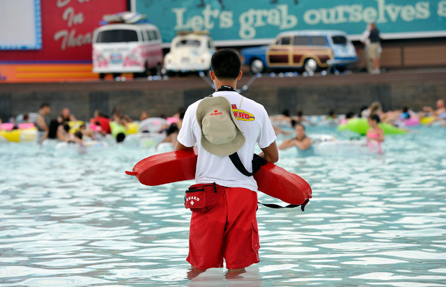 A lifeguard keeps his eyes on swimmers in the wave pool during the opening day of Cowabunga Bay in Henderson on Friday, July 4, 2014. After several delays the water park opened with  25 water slid ...