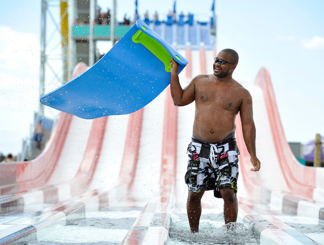 Ernest Hall of North Las Vegas celebrates his victory down the Surfin' USA mat racer slide during the opening day of Cowabunga Bay in Henderson on Friday, July 4, 2014. After several delays the wa ...